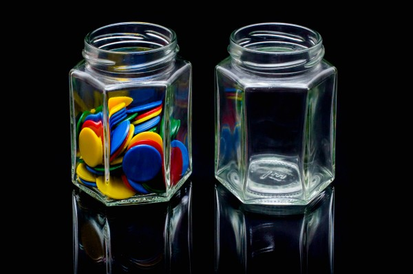 Two small jam jars, one full of plastic counters, one empty.